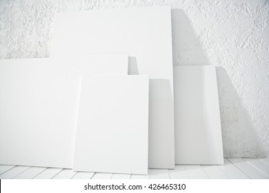 WHITE  CANVASES IN DIFFERENT SIZES , ON WHITE WOOD FLOOR IN FRONT OF ROUGH WHITE WALL