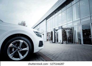 White car. White comfortable luxury passenger car standing outside in front of car salon