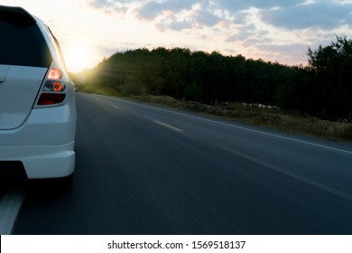 White car driving on the asphalt road with sunlight and forest in evening.