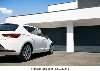 White car in front of modern house waiting to enter in the garage with large garage door