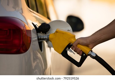 white car at gas station being filled with fuel