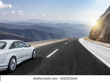 White car moves on the road among the mountains and forests.