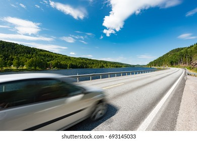 White car on country road in Norway, Europe, Scandinavia. Auto travel on sunny day. Blue sky with clouds.