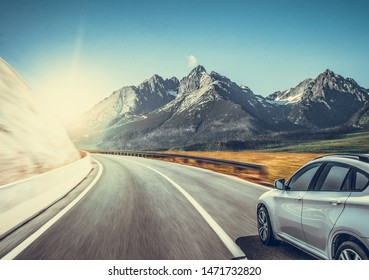 White car on a mountain road. Highway among the mountain scenery. Toned photo.