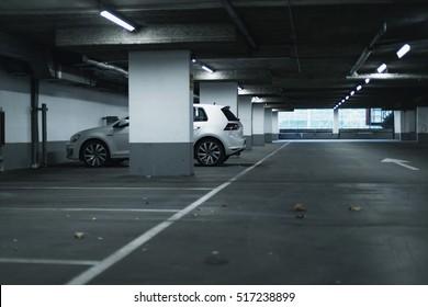 White car parked in empty parking garage.