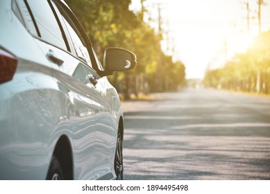 White car parked on the roadside, with natural backgrounds with bright sunlight.