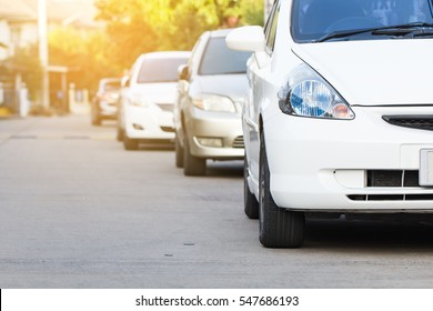 White car parked in a row on the road, outdoor parking