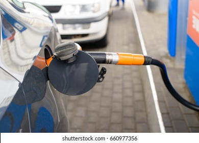 white car at petrol station being filled with petrol