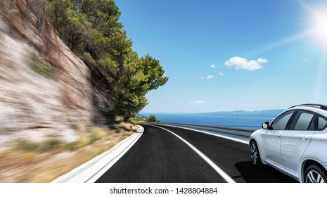 White car rushes along the road to the sea. Motion blur effect.