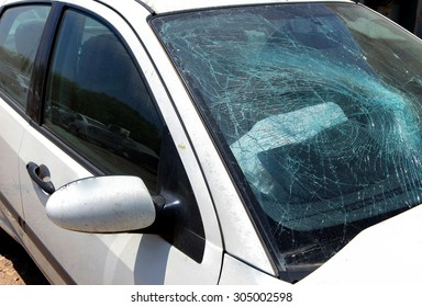 White car with smashed windshield