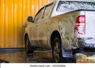 White car with white soap on the body in car care shop.