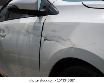 The white car that was struck by another car caused damage to the side.