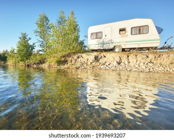 White caravan trailer parked on the rocky river shore on a sunny day. Clear blue sky. Ba;tic states, Europe. Summer vacations, travel, ecotourism, recreation, off-grid camping, road trip, RV
