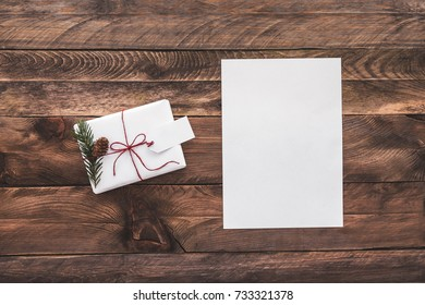 White card and a white gift. Christmas background. View from above. Flat lay