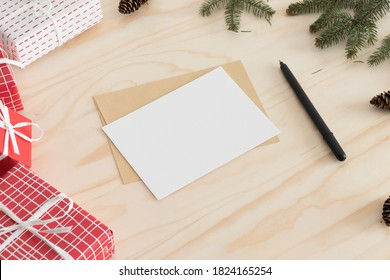 White card mockup with christmas decoration on a wooden table.