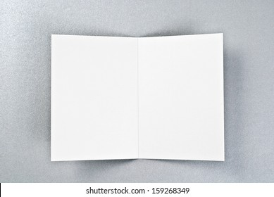 White card or sheet of paper over silver background