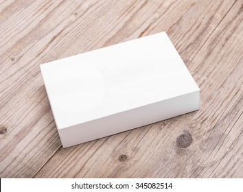White cardboard box on a wooden background.