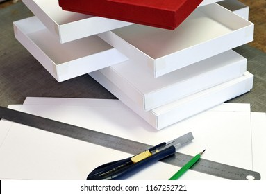 White cardboard boxes lined with red paper made by hand to contain gift objects