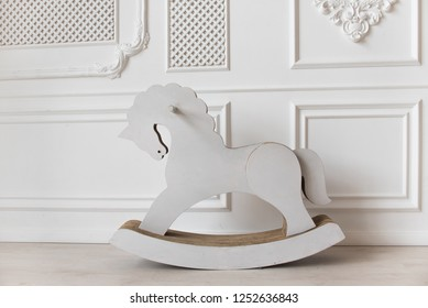 white cardboard horse, children's toy swinging. interior white wall.