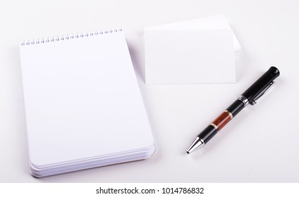 White cards next to notebook and black pen on white background. Isolated. Mockup.