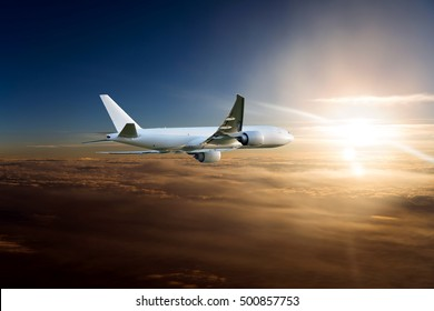 White Cargo plane in the sunset sky. Aircraft flying above the colorful clouds on a background of the bright sun.
