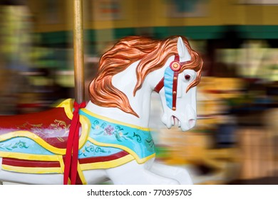 A white carousel horse in motion