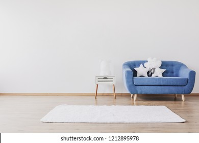 White carpet, blue sofa and cute pillows in elegant child's room with posters on the wall, real photo