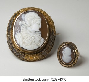 White carved woman's face on brown background with gold setting cameo brooch and matching ring.