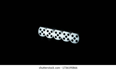 White casino dice. Dice isolated on a black background. The dice are white with black dots