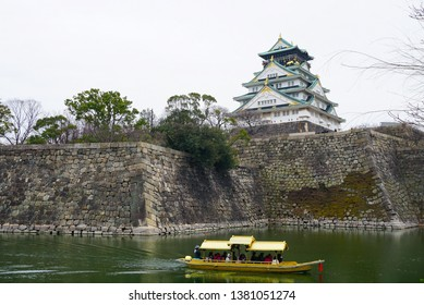 The white castle is located along the walled river in Japan.