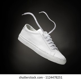 White casual shoes on black background