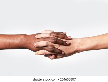 white Caucasian female hands and black African American holding fingers together in world unity and racial love and understanding in tolerance and races diversity cooperation concept isolated close up