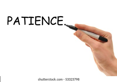 White Caucasian hand writes the word Patience on the whiteboard with a marker