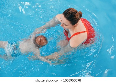 White Caucasian mother traning her newborn baby to float in swimming pool. Baby diving in water. Healthy active lifestyle. Family activity and early development concept