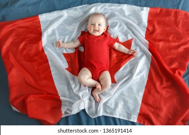 White Caucasian smiling baby boy girl with blue eyes lying on large Canadian flag with red maple leaf. Newborn infant kid in red onesie romper celebrating national Canada day. View from top above