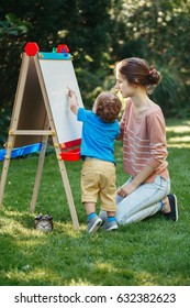 White Caucasian toddler child kid girl with older sister, teacher standing outside in summer autumn park drawing on easel with markers, playing studying learning, back to school