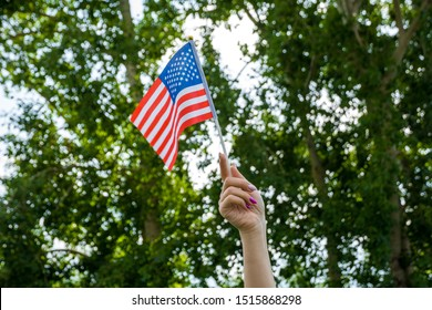 White Caucasian woman hand arm waving USA flag on blue sky and green forest