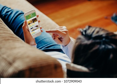 White caucasian woman using a mobile phone to book hotel for vacation while rest on the sofa at home. She is touching phone screen.