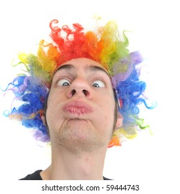 A white Caucasian young adult wearing a silly clown wig with rainbow colorful hair.