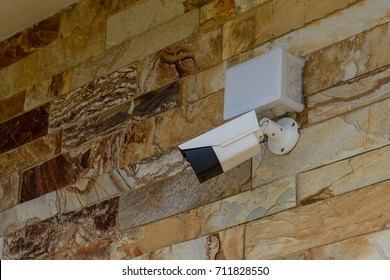 white CCTV camera on a stone wall
