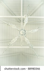 White ceiling fan on a white ceiling, with white boards