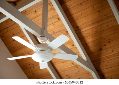 White ceiling fan on an exposed support beam, with a vaulted wood ceiling, in the living room of a modern home, with space for text on top and right side