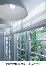 White ceiling lamps next to the windows, with the white curtain. Outside the window are green plants.