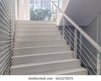 White Cement Staircase with Steel Balustrade and Aluminium Battens Wall ,Selective Focus.