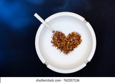 White ceramic ashtray with cigarette smoke and heart shaped dry tobacco leaf