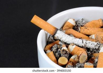 White ceramic ashtray detail full of smokes cigarettes