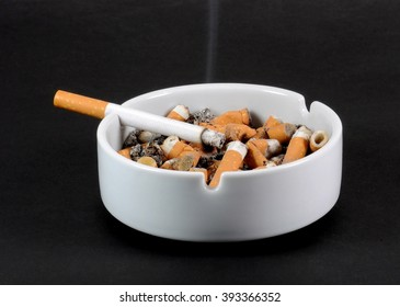 White ceramic ashtray full of smokes cigarettes