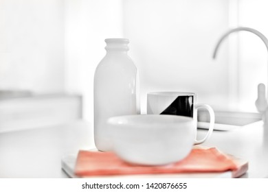 White ceramic bottle in  background with the sunlight in a kitchen, there is blurred mug near it,  the mug is beside the napkin, very clean area.