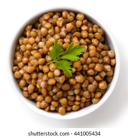 White ceramic bowl of brown cooked lentils with parsley isolated on white from above.