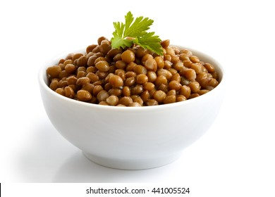 White ceramic bowl of brown cooked lentils with parsley isolated on white in perspective.